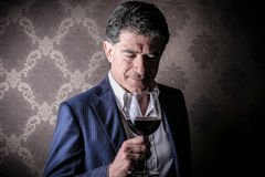 Man with a glass of wine. Elegant rich man with a glass of wine royalty free stock images