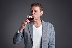 Man with glass of wine. A middle age man drinking and tasting a glass red winer Royalty Free Stock Images