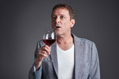 Man with glass of wine. A middle age man holding and smelling a glass of winer Royalty Free Stock Photo