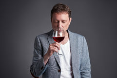 Man with glass of wine. A middle age man holding and smelling a glass of winer Stock Images