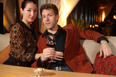 Man  and a woman looking at the camera. Man with a glass of wine and a women looking at the camera Stock Images