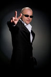 A man with glasses. Secret service agent with open palm  on black background Royalty Free Stock Photos