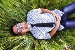 A man in glasses. A handsome young man in glasses lying on green grass with eyes closed Stock Images