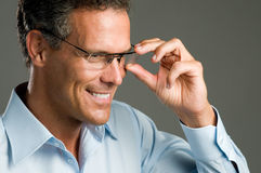 Man with glasses. Handsome mature man holding a pair of modern glasses Stock Image