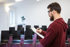 Man in glasses with beard making notes standing profile Royalty Free Stock Image