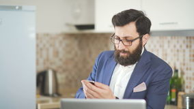 Man in glasses with a beard working in homeoffice: phone and laptop stock video footage