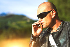 Man with glasses and black jacket smoking cigarette Royalty Free Stock Image