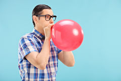Man with glasses blowing up a balloon Royalty Free Stock Photo
