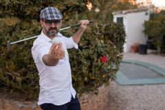 Man showing golf ball in his hands with golf club on his back stock image