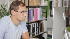 Man with glasses carefully looks at monitor screen in the office.