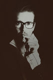 Man in glasses with cigarette on black background Stock Photography