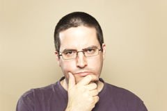 Man in glasses considers Royalty Free Stock Photography