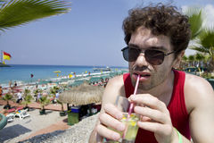 Man in glasses drink cocktail Mojito on beach Stock Image