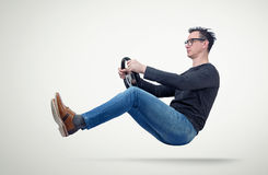 Man in glasses drives a car with a steering wheel Royalty Free Stock Photos