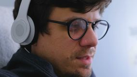 Man in glasses and headphones listening music and singing a song. Face close-up. Man in glasses and earphones listening music and singing a song. Face close-up stock video