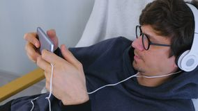Man in glasses and headphones playing a game in smartphone. Gamer relax. Man in glasses and earphones playing a game in smartphone. Gamer relax stock footage