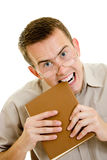 The man in glasses eats book. Stock Image