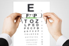 Man with glasses and eye chart. Medicine and vision concept - man looking at eye chart through eyeglasses royalty free stock photo