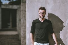 Man in glasses in front of concrete wall. Angry handsome young bearded hipster guy in casual outfit and eyeglasses is leaning against the wall on a sunny day Stock Images
