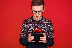 A man in glasses with a gift box in his hands, looks at her, on a red background stock images