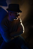 Man with glasses and a hat sitting in the dark Stock Images