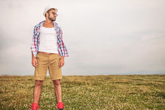 Man with glasses and hat standing in a field Royalty Free Stock Images