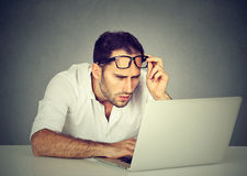Man with glasses having eyesight problems confused with laptop Royalty Free Stock Images