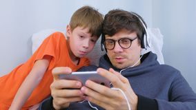 Man in glasses and headphones playing a game in smartphone with his son. Gamer relax. Man in glasses and headphones playing a game in smartphone with his son stock footage