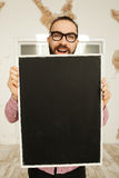 Man in glasses holding blank blackboard in hands Stock Image
