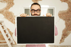 Man in glasses holding blank blackboard in hands Stock Images