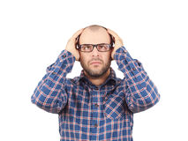 Man with glasses holding his head with his hands. Stock Images