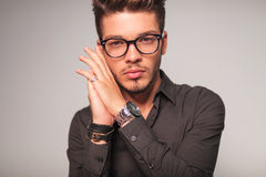 Man with glasses  holding  palms together near his face Stock Photography