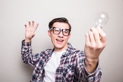 Man in glasses holding small light bulb Stock Photos