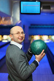 Man in glasses holds ball for bowling. Man in glasses stands sideways and holds  ball for bowling Royalty Free Stock Image