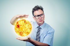 Man in glasses holds in hands of the sun Royalty Free Stock Photo