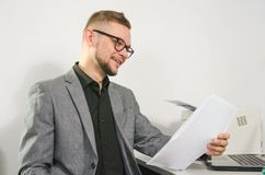 Man with glasses and jacket smiles studying documents Royalty Free Stock Images