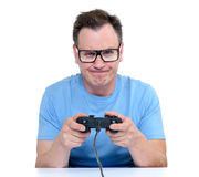Man in glasses with a joystick playing in game on white background Royalty Free Stock Photos