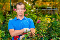 Man in glasses and laboratory gloves in a greenhouse Stock Photo