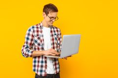The man in glasses with a laptop, on a yellow background stock photo
