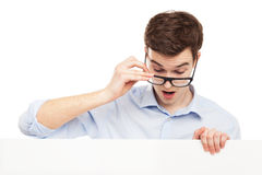 Man in glasses looking at blank sign Royalty Free Stock Photography