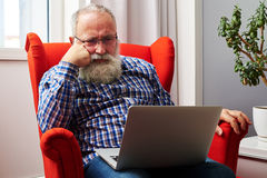 Man in glasses looking at laptop. Bearded senior man in glasses sitting on the red chair and looking at laptop royalty free stock photo