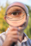 Man with glasses looking through magnifier Stock Photo