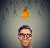Man in glasses looking up at bright idea light bulb above head Royalty Free Stock Image