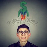 Man in glasses looking up at rocket dollar sign above head Royalty Free Stock Images