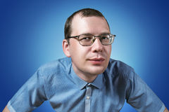 Man in glasses. Looking at you on the blue background Royalty Free Stock Photography