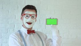 Man in glasses looks into the smartphone. Cheerful mime in a white shirt with a smartphone in his hand. green screen