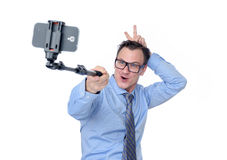 Man in glasses making selfie with a stick Stock Images