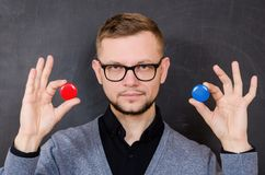 A man with glasses offers to choose one of the options. Choosing a red or blue chip Royalty Free Stock Photo