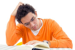 Man with glasses in orange sweater reading book. Adult handsome man with glasses in orange sweater reading book Stock Photo