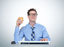 Man with glasses and a paper cup at the keyboard in front of computer. Programmer at work Stock Photography
